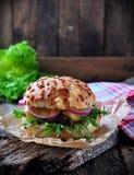 水多的汉堡用牛肉、乳酪、莴苣、酸黄瓜、烂醉如泥的葱和乳酪大面包 库存照片