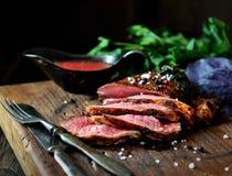 水多的烤肉片在一把切板、蓬蒿、荷兰芹、香料、葡萄酒刀子和叉子的在黑暗的背景的da 免版税库存照片