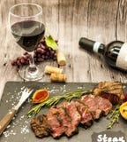 水多的牛排striplon特写镜头与瓶和一杯的在一块黑石板材的红葡萄酒在一张木桌上 免版税库存照片