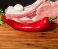 水多的肉片在骨头的用红辣椒荚,荷兰芹和大蒜在一张木桌上说谎 免版税库存图片