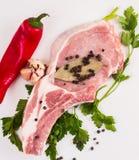 水多的肉片在骨头的用红辣椒荚,荷兰芹和大蒜在一张木桌上说谎 免版税库存照片