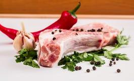 水多的肉片在骨头的用红辣椒荚,荷兰芹和大蒜在一张木桌上说谎 图库摄影