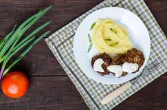 水多的肝脏炸肉排用调味汁和土豆泥在一块白色板材 免版税图库摄影