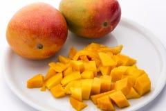 水多的芒果模子和两个整个芒果在板材 图库摄影