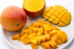 水多的芒果立方体和整个果子堆在板材 图库摄影