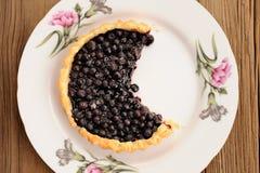 水多的蓝莓馅饼在有桃红色康乃馨的白色板材切开了在w 免版税图库摄影