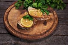 水多的被烘烤的三文鱼用柠檬和草本 库存图片