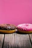多福饼与在木桌和桃红色背景上洒 油炸圈饼的两种类型 蛋糕和甜点 食物细节 关闭 淡色col 库存照片