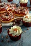 多福饼圆环和香草焦糖杯形蛋糕与白色和黑暗的巧克力碎片和结冰在船上服务 库存照片