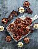 多福饼圆环和香草焦糖杯形蛋糕与白色和黑暗的巧克力碎片和结冰在船上服务 免版税库存图片