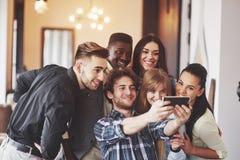 多种族人民获得乐趣在采取与手机的咖啡馆一selfie 坐在餐馆的小组年轻朋友 免版税图库摄影