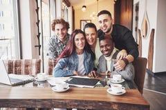 多种族人民获得乐趣在采取与手机的咖啡馆一selfie 坐在餐馆的小组年轻朋友 免版税库存图片