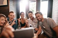 多种族人民获得乐趣在采取selfie的咖啡馆 免版税图库摄影