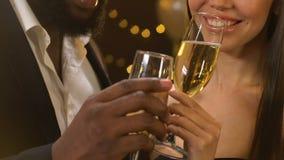 多种族夫妇使叮当响的玻璃用香槟和聊天在党,调情的人 影视素材