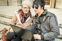 多种族夫妇获得乐趣使用膝上型计算机 免版税库存图片