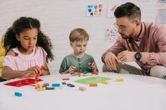 多种族学龄前儿童和老师有雕刻图的彩色塑泥的在桌上 库存照片