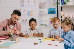 多种族学龄前儿童和老师有雕刻图的彩色塑泥的在桌上 免版税库存图片