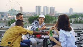 多种族小组朋友使玻璃,饮用的软饮料叮当响并且吃薄饼在桌上坐屋顶 股票视频