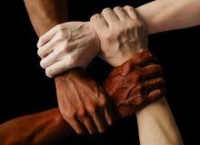 多种族小组用举行的黑非裔美国人的白种人和亚洲手在容忍团结爱的腕子和反 库存图片