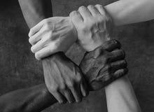 多种族小组用举行的黑非裔美国人的白种人和亚洲手在容忍团结爱的腕子和反 免版税库存图片