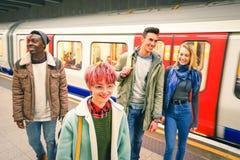 多种族小组行家朋友获得乐趣在管地铁 免版税库存图片