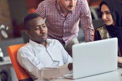 多种族当代商人工作连接用象片剂和膝上型计算机的技术设备 库存图片