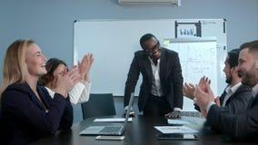 多种族集团招呼有拍手和微笑的美国黑人的上司 免版税库存图片
