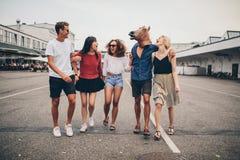 多种族年轻朋友获得乐趣一起在街道上 库存图片