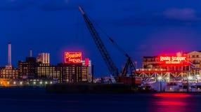 多米诺在晚上加糖工厂和生锈的甲板排水孔餐馆,巴尔的摩,马里兰 库存照片