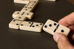 多米诺比赛在一张黑暗的桌上的 多米诺比赛的概念  人有多米诺的` s手 关闭 免版税库存图片