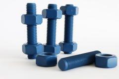 多缩木胶螺栓和坚果在蓝色用PTFE涂 库存照片