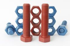 多缩木胶螺栓和坚果在蓝色用PTFE涂 免版税图库摄影