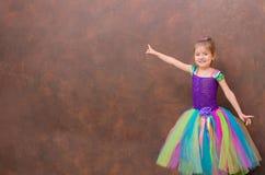 多色芭蕾舞短裙的女孩指向棕色墙壁的 免版税库存照片