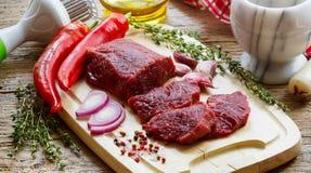 贝多芬 在切板、橄榄油、大蒜、辣椒、麝香草和香料的新鲜的生肉 免版税库存图片