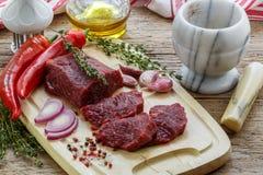 贝多芬 在切板、橄榄油、大蒜、辣椒、麝香草和香料的新鲜的生肉 库存图片