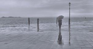 多雨和老保守天在有孤独的妇女的威尼斯有伞的和在backround的喜怒无常的海景 库存照片
