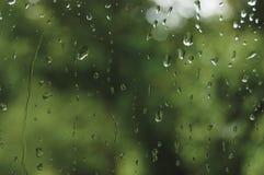 多雨夏日,在湿玻璃窗,水平的明亮的抽象雨水背景样式细节,宏观特写镜头的雨珠 图库摄影