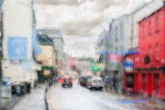 多雨天气和城市雨珠在玻璃窗流动 免版税库存图片
