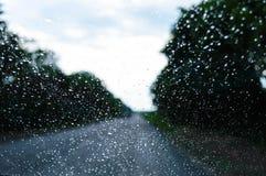 多雨天气的看法通过沿路乘坐汽车的挡风玻璃 库存照片