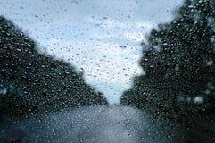 多雨天气的看法通过沿路乘坐汽车的挡风玻璃 免版税库存照片