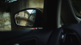 多雨平衡的街道的反射在移动驾车的旁边镜子的在一个小地中海镇 ?? 股票录像