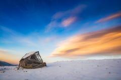 多雪的小山的老打破的木房子 免版税库存图片