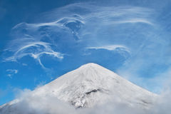 多雪的山、奇怪的分散的云彩和雾横向  库存图片
