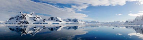 多雪的山和冰山的完善的镜象反射在南极洲 图库摄影