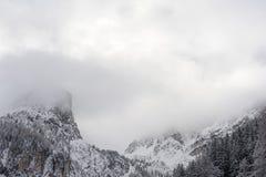 多雪的山峰和山脉和与云彩和薄雾在冬天在奥地利阿尔卑斯在Stubai 免版税库存照片