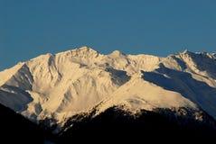 多雪的山峰在黎明 库存照片