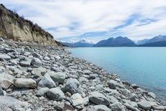 多雪的山峰的看法在一个蓝色湖的 免版税库存照片