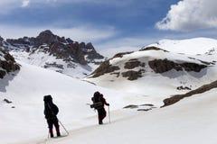 多雪的山的两个远足者 库存照片
