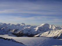 多雪的山 在蓝色山的太阳黎明 在山的领域 免版税库存照片
