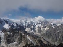 多雪的岩石山上面在多云背景的 库存图片